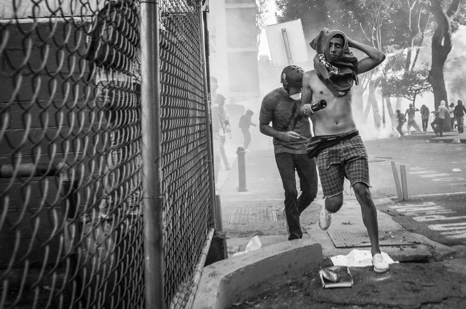 Demonstrators run away after being targeted with a tear gas during the protest on Avila Avenue in Altamira, Caracas.  Altamira has been the main area where students have been demonstrating on the last days in the Venezuelan capital against the Government of President Nicolas Maduro.