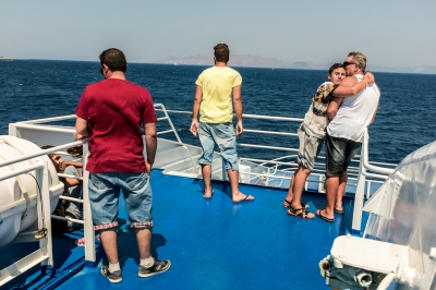 KOS, GREECE — AUGUST 20, 2015: In his yellow shirt, Omar from Iraq, is onboard the ferry bound to Kos Island from Rhodes. Accompanied on the top deck by a Syrian travel companion (red shirt) and some French tourists (right). Once on the island of Kos, Omar hopes to be assisted by the Greek authorities in order to reach Athens and continue his journey towards Germany.