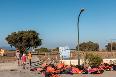 KOS, GREECE — AUGUST 20, 2015: Tourists stroll past an array of life vests cast away by migrants after they disembarked.
