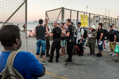 KOS, GREECE — AUGUST 20, 2015: The police are enforcing strict control of regulation papers, which determines who is entitled to board the ferry to Piraeus, near Athens. Most refugees are on their way to the Western and Northern wealthier European countries.