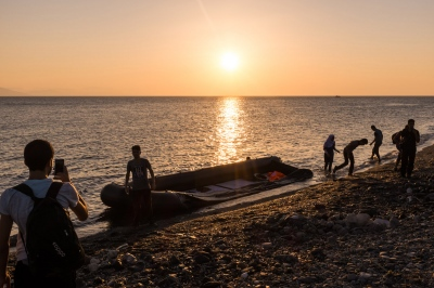 KOS, GREECE — AUGUST 21, 2015: A group of Syrian refugees are enjoying the end of their sea trip in the light of dawn. 'Selfies' and the use of social media are essential to show the progress of their journey to their families left behind.