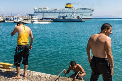 KOS, GREECE — AUGUST 22, 2015: Syrian teenagers from Etlib dive in the harbor, while the Eleftherios Venizelos ship departs to bring refugees to the mainland.