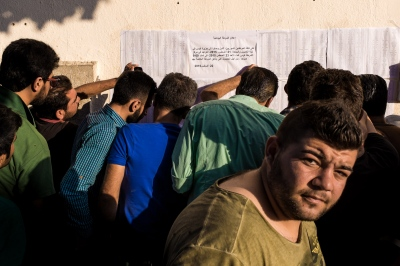 KOS, GREECE — AUGUST 23, 2015: A group of men are looking for their names on the list outside the Police Station in the town of Kos. The process for issuing travel documents has been streamlined by the Greek authorities.