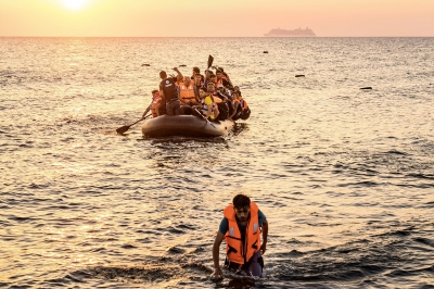 KOS, GREECE — AUGUST 21, 2015: Approximately 40 Syrian refugees are aboard a rubber dinghy, seeking a safe place to land on Kos' shores. The illegal overnight trip on the Aegan Sea from Bodrum can take up to 3-4 hours.