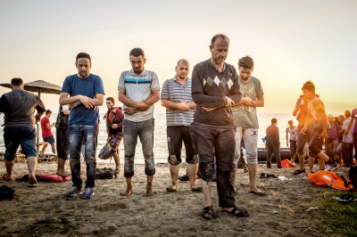 KOS, GREECE — AUGUST 21, 2015: As soon as he set foot on land, Mohammed Nahji, 45, led the prayer to thank God for their safe arrival. He was a sports teacher in Deir Ezzor, Syria. Following the recent bombing, he left his wife and four children behind to find a way to support them financially.