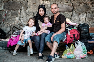 KOS, GREECE — AUGUST 22, 2015: Omar, 35, and Lobna, 26, are from Deir Ezzor, Syria. They were successful in crossing from Bodrum to Kos on their second attempt. They had to pay 1,400 euros per adult plus 700 euros per child: Lana, 4, and Lean, 14 months. Their final destination is Germany along with other refugees. Germany could host up to 800,000 refugees this year. This number has multiplied four times, in comparison to 2014.