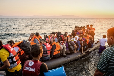 KOS, GREECE — AUGUST 21, 2015: Approximately 40 Syrian refugees are aboard a rubber dinghy about to dock in Kos. 50,000+ refugees have completed the crossing to Greece in July 2015 alone, which represents more refugees than for the whole year of 2014.