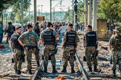 GEVGELIJA, MACEDONIA — AUGUST 25, 2015: The Macedonian riot police is to control the growing influx of migrants at the Greek border. Following the declaration of a state of emergency on August 20, the border police allow groups of only 50 people to pass through at a time.