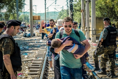GEVGELIJA, MACEDONIA — AUGUST 25, 2015: A group of refugees are given authorization to illegally cross over the Greek-Macedonian border to pursue their journey into Europe.