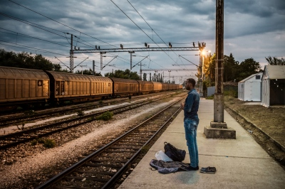 """TABANOVTSE, MACEDONIA — AUGUST 25, 2015: Hussein, from Chichiga, Somalia, is praying in the early evening at a train station hundred meters aways from the Serbian border. He is still unsure about his final destination but he says that he has """"a good feeling about Germany""""."""