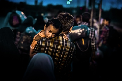 TABANOVTSE, MACEDONIA — AUGUST 25, 2015: A young child rests on his father's shoulder after a few hundred refugees disembark from a train, which arrived from Gevgelija. This group of refugees is making their way towards Serbia on foot.
