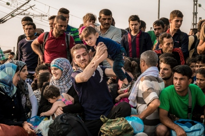 IDOMENI, GREECE — AUGUST 26, 2015: Refugees patiently await their turn at the Greece/ Macedonia border, in order to be given authorization to cross illegally into Serbia.
