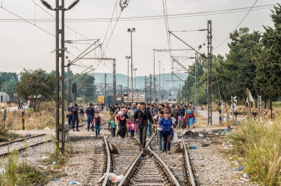 IDOMENI, GREECE — AUGUST 26, 2015: A few hundreds of refugees are spontaneously walking towards Macedonia despite the Greek police efforts to contain the influx. Nowadays, up to 3,000 people are crossing the border every day.
