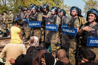 IDOMENI, GREECE — AUGUST 26, 2015: The Macedonian riot police is lined up to control the influx of refugees entering the country. After the border was shut, and following the clash on August 21 between refugees and police, small groups are now allowed to enter once at a time.