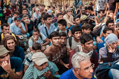 IDOMENI, GREECE — AUGUST 26, 2015: Refugees are seated, in order to keep the crossing organized. Since end of June 2015, an estimated 40,000+ refugees have passed through Macedonia en route to EU.