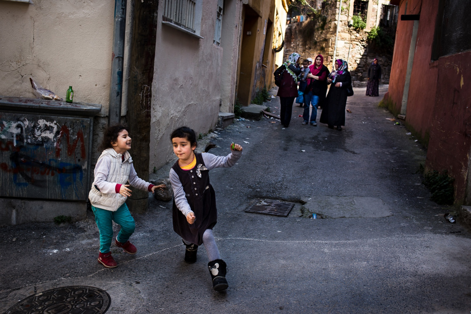 Two young girls chase each other in the Kadifekale neighborhood of Izmir, Turkey. This area of Izmir, a poor area once mostly home to Kurds, is now home to many Syrians coming from Aleppo. For many, Izmir is one of the final stops on the migration route to the European Union.