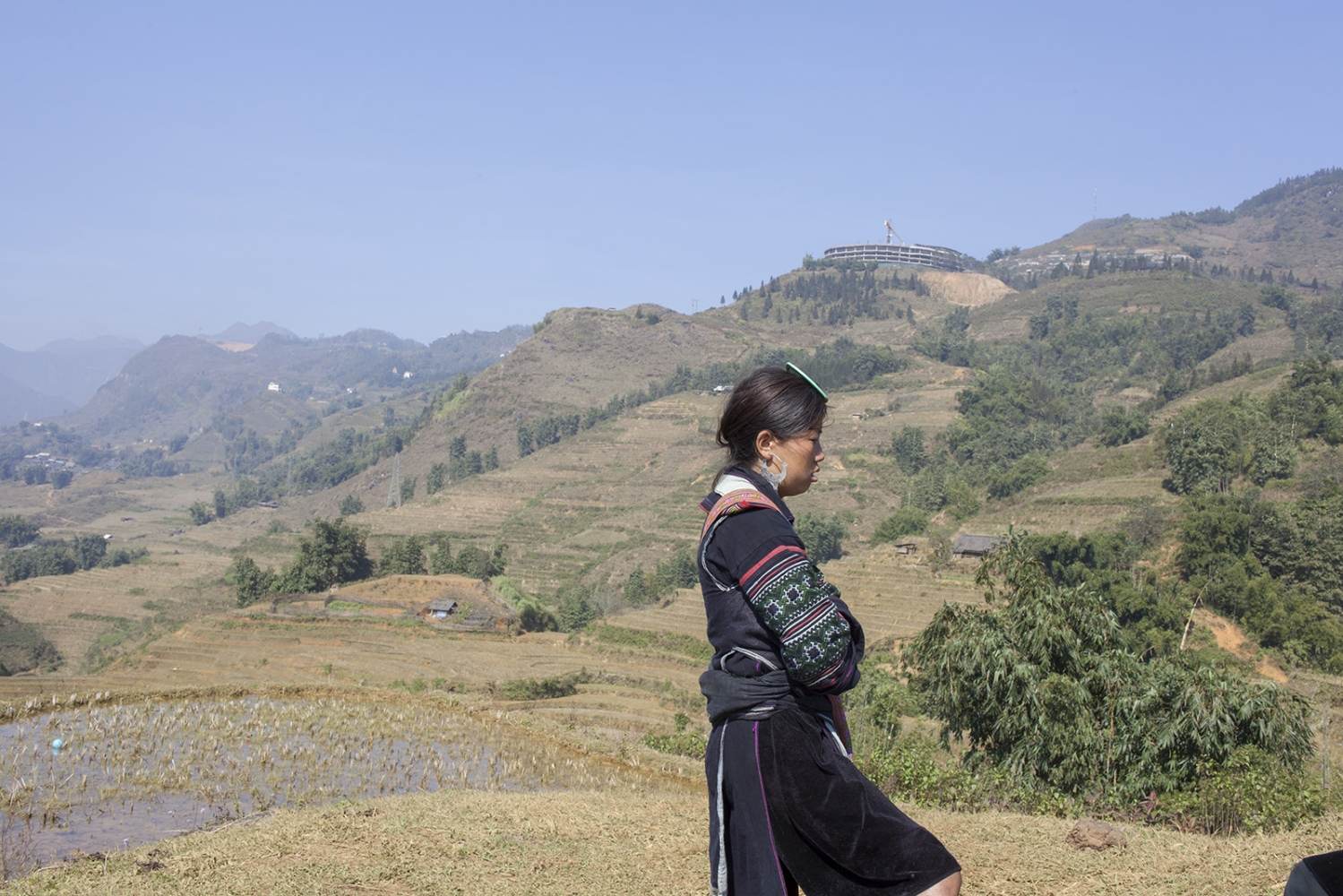 Black Hmong woman with the valley in the background. On the hill over her head, a big tourist hotel is under construction.
