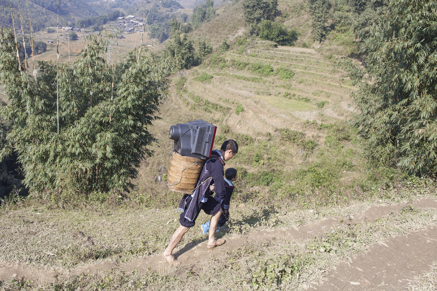 Man carrying a TV up the steep hills.