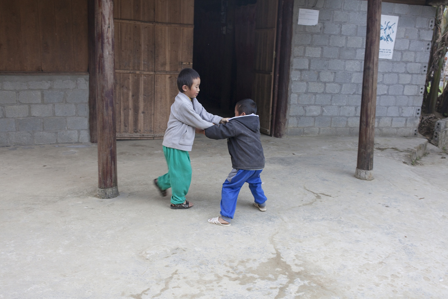 Two kids play fighting.