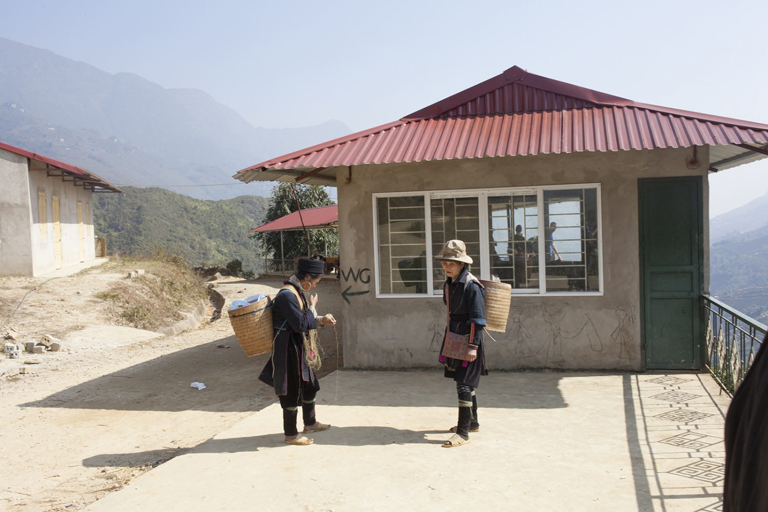 Two Hmong ladies having a break from trying to sell handicrafts to tourists.