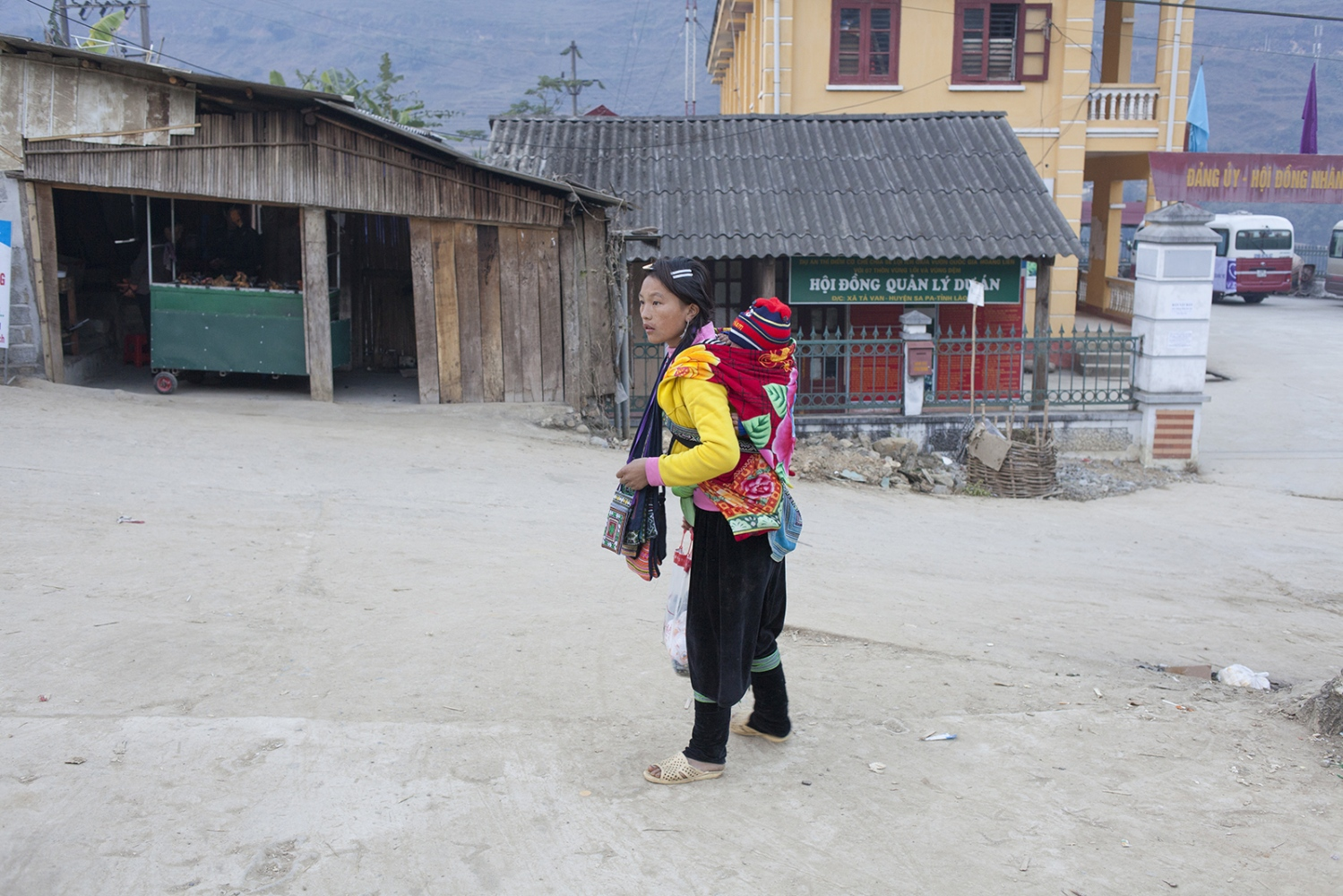 Woman with child in a harness on her back.