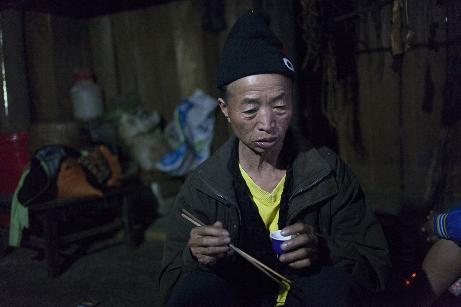 A Hmong man drinking rice wine. The men are out of work for most for the winter and an over consumption of rice vine is common.