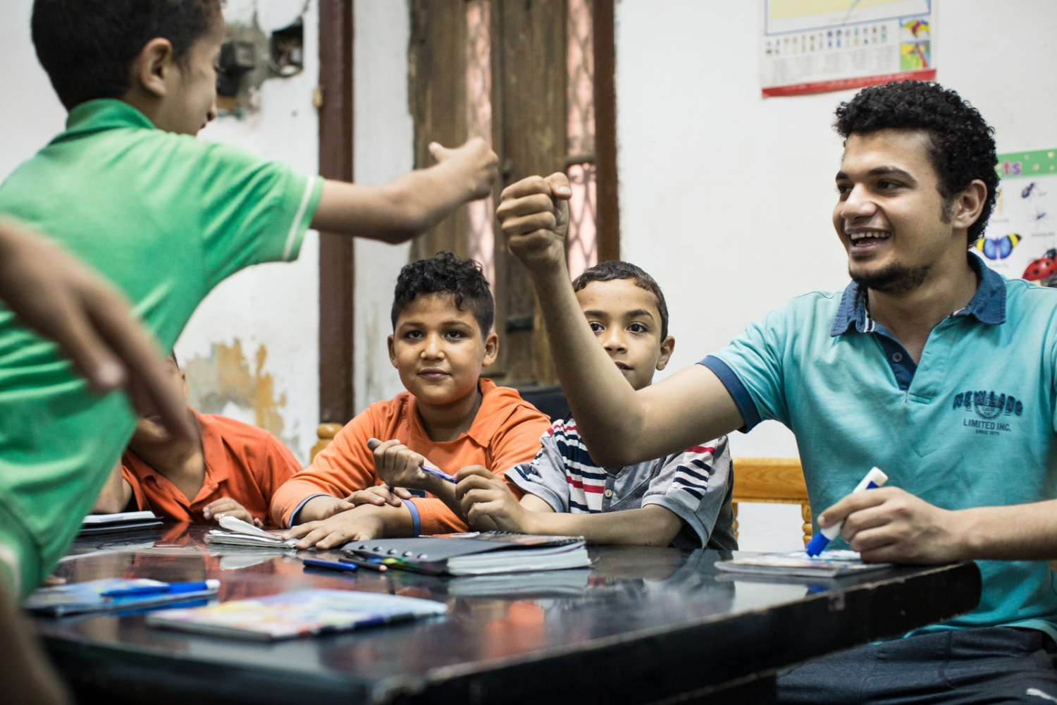 p.p1 {margin: 0.0px 0.0px 0.0px 0.0px; font: 10.0px 'Lucida Grande'} Mostafa fist-bumps a student when he gets the right answer during French class. Mish Madrasa is a grassroots volunteer group that provides tutoring and after school activities to poor children in Saft el Laban, a slum neighborhood of Cairo.