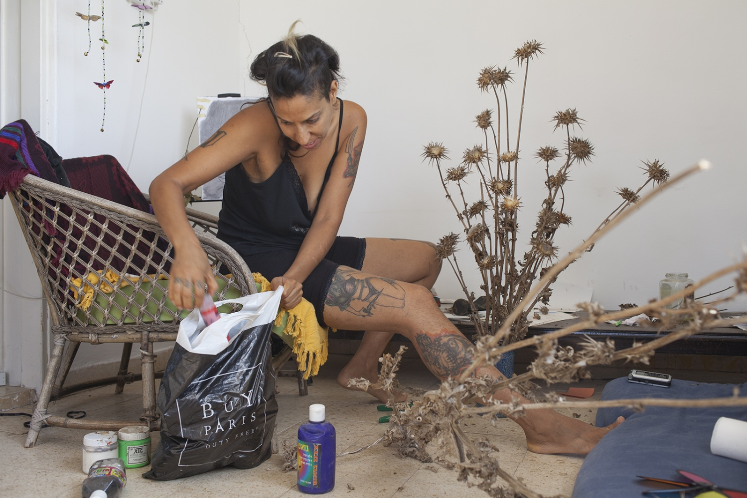 Zina painting flowers in her house in the desert outside of Tel Aviv.