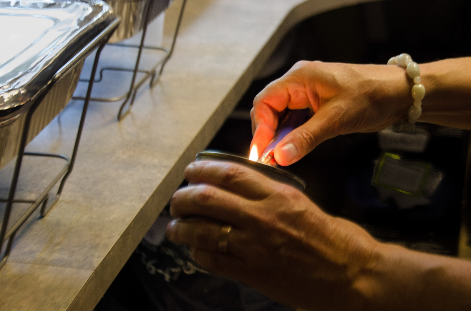 Kelly lights a burner to keep food warm for RAD's regular weekend lunch delivery to University Bikes on Pearl Street.