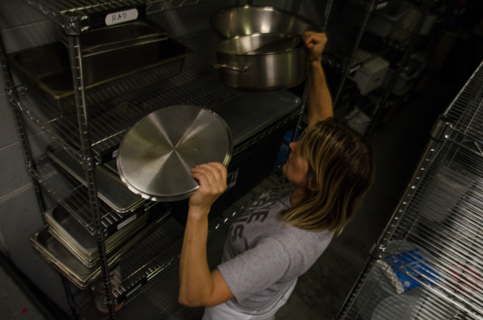 Kelly looks for the right pots and pans in the shared commissary space in preparation for a full list of orders for the next day.