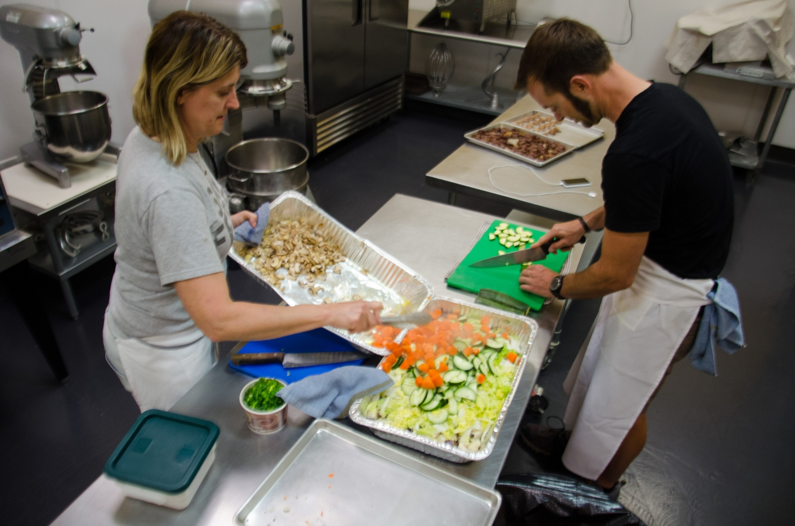 Chef Kelly and Morgan chop, cook and mix a variety of ingredients to create the ordered dishes to deliver.