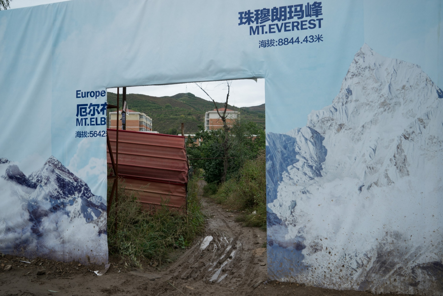Huge board covered by pictures of the world's highest mountains in Chongli County.