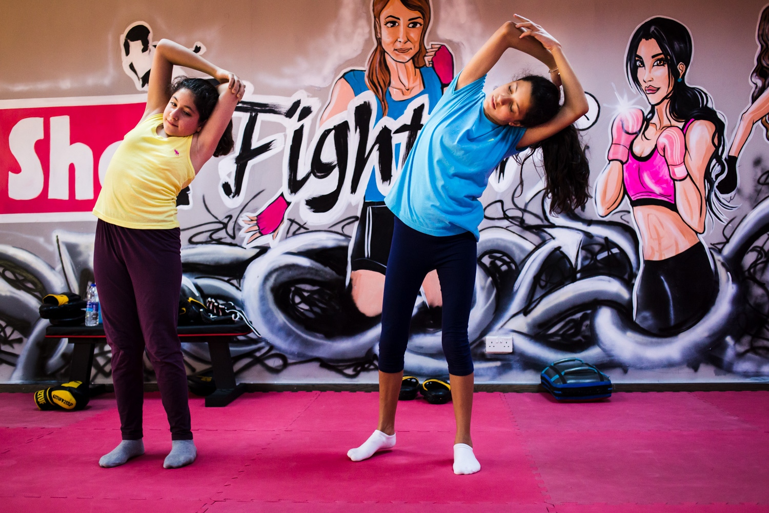 Sana Kayyali and Reem Habib stretch and do yoga poses in between kicking and punching exercises during a self defense class at She Fighter in Amman, Jordan, on August 21, 2015. The She Fighter studio was founded by Lina Khalifeh, and offers self defense classes to young women to protect against harrassment.