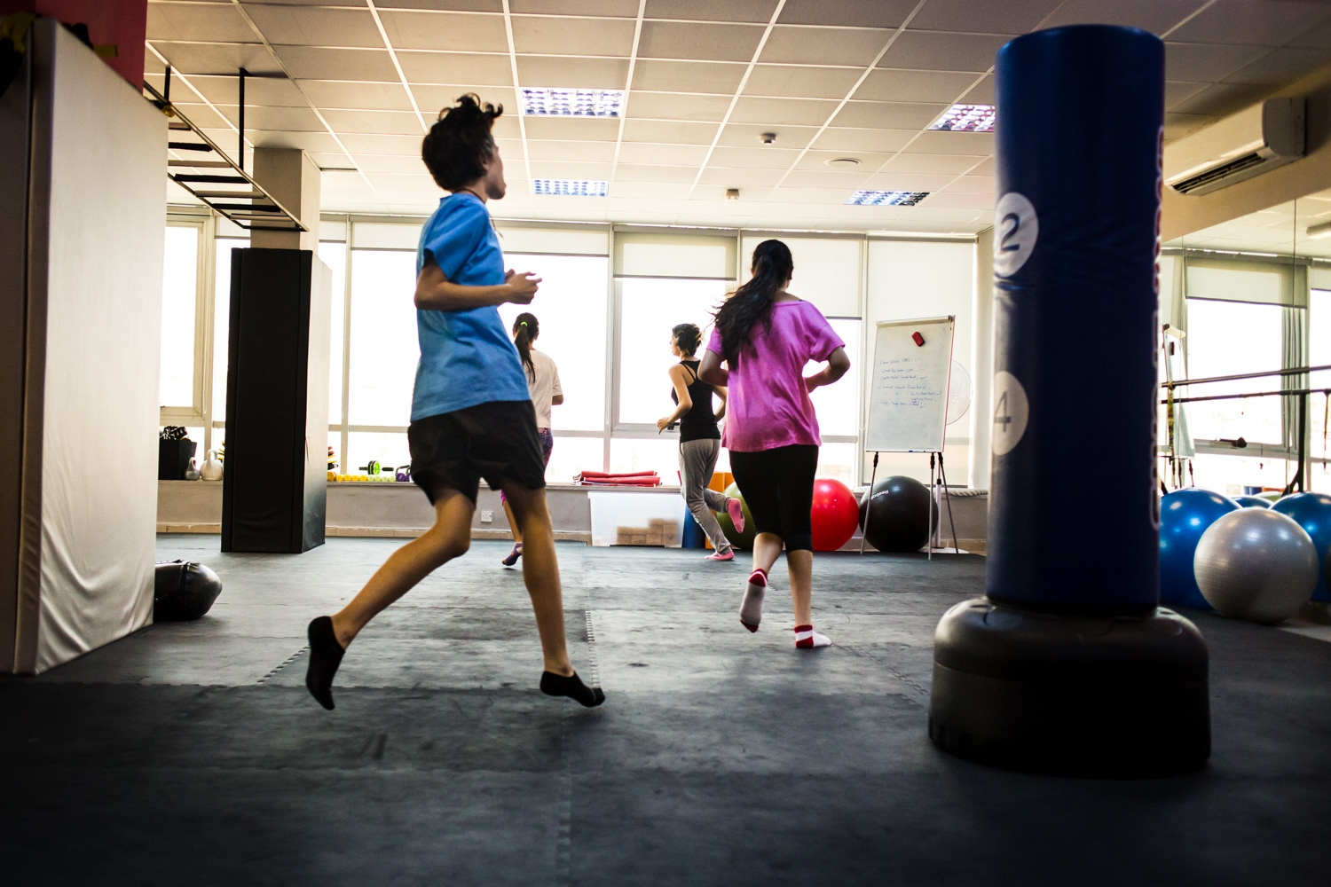 Girls run laps around the studio to warm up for the next lesson in a self defense course at She Fighter in Amman, Jordan, on August 21, 2015. The She Fighter studio was founded by Lina Khalifeh, and offers self defense classes to young women to protect against harrassment.