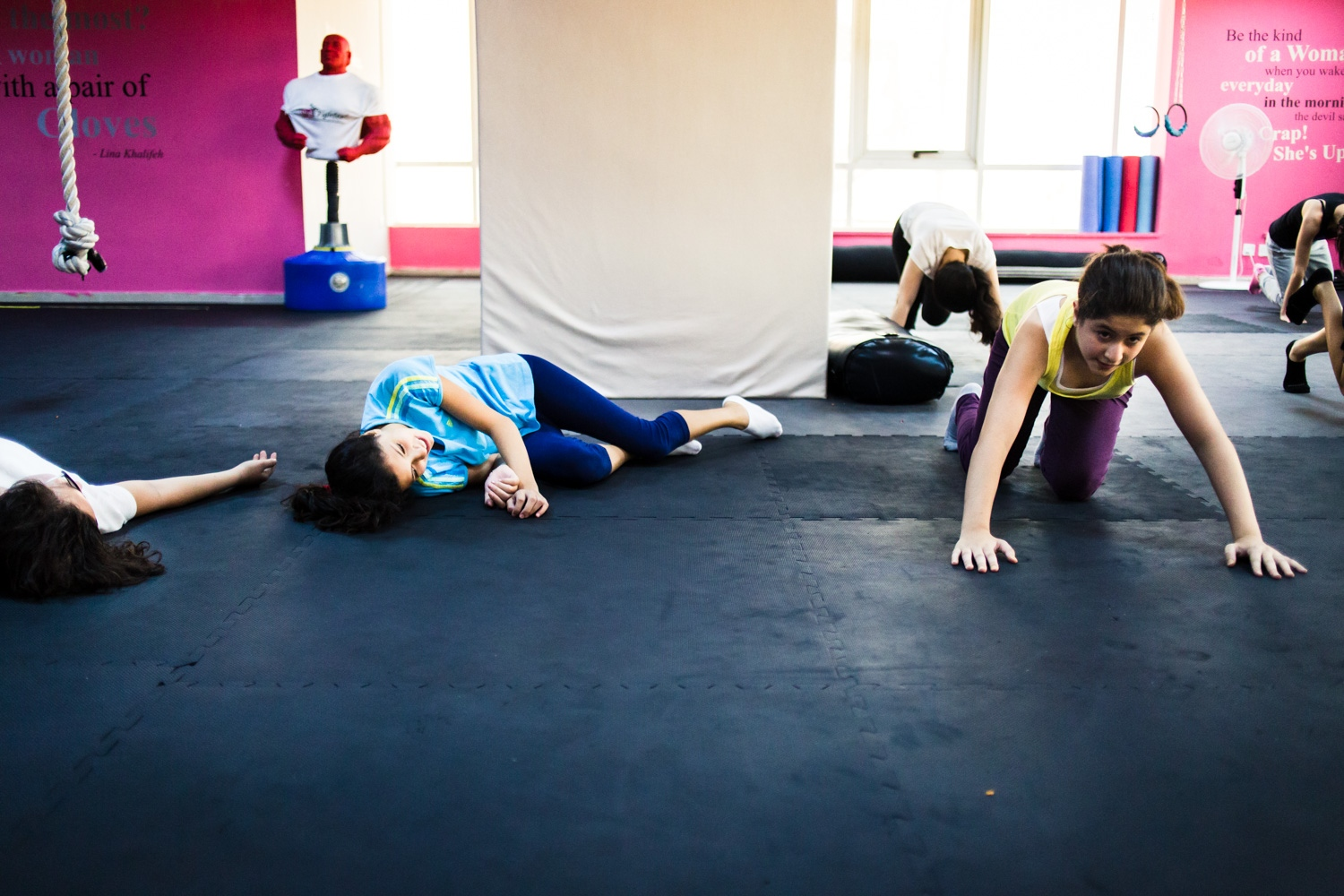 Reem Habib collapses on the floor, laughing, after holding the plank position during a self defense class in Amman, Jordan, on August 21, 2015. The She Fighter studio was founded by Lina Khalifeh, and offers self defense classes to young women to protect against harrassment.