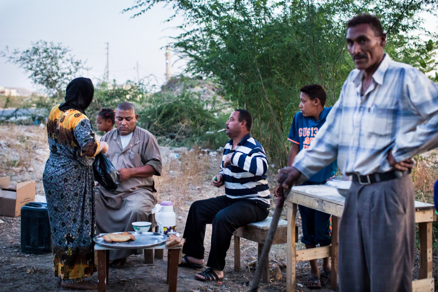 Residents of Ghor Safi sit together and talk at dusk, baking bread on an outdoor oven.