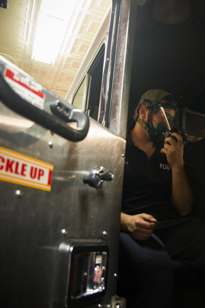 Fireman Eric Dini checks to make sure oxygen masks within the fire engine are working. Dini has been a fireman at Firehouse 235 since 2004.