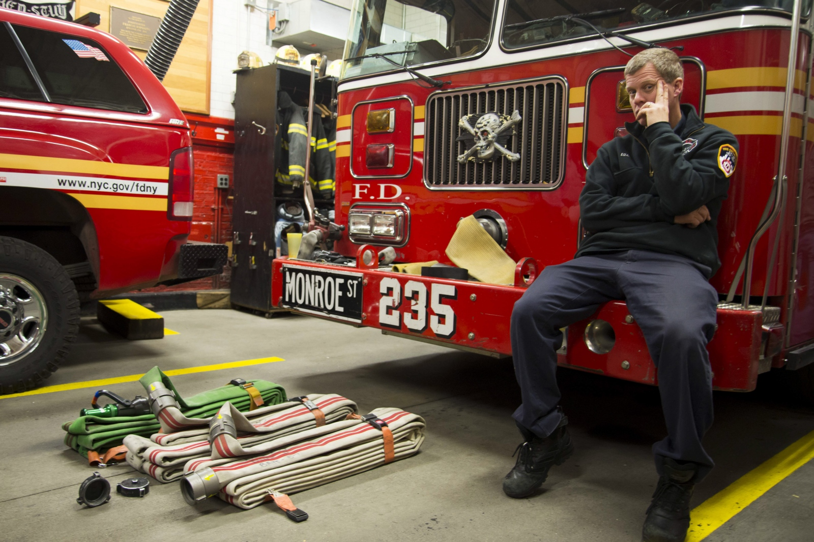 Fireman Bill Egan sits on the front of his engine. Tonight, he is the driver.
