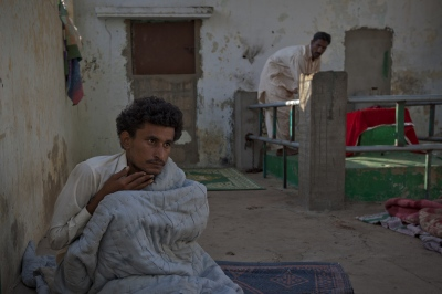 Pakistani resident Muhammad Rehan, 18, believed to be possessed by a demon, sits by the wall he has been chained to for four months at the shrine of spiritual leader Hazrat Abdullah Shah Ashabi in Makli in the district of Thatta in Pakistan's Sindh province on November 24, 2011.