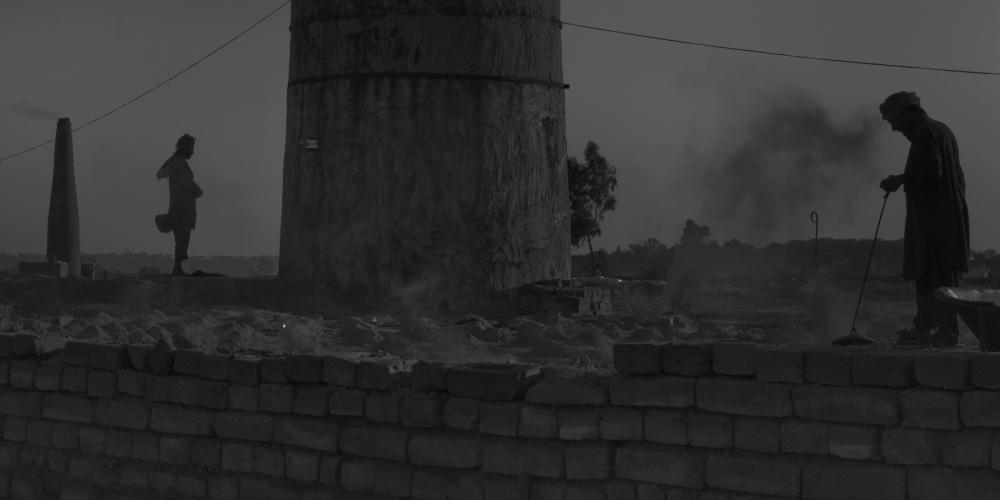 A Pakistani labourer (L) offers evening prayers at a brick factory on the outskirts of Rawalpindi on November 12, 2011.