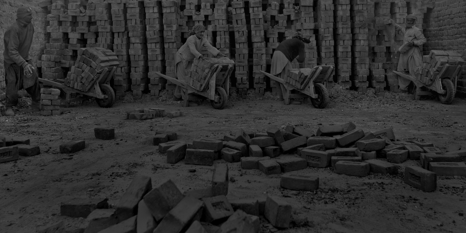 Pakistani labourers move bricks from the inside of a kiln to transport them from a brick factory on the outskirts of Islamabad on January 11, 2012.