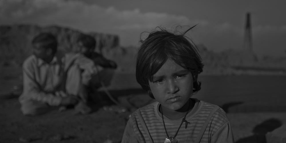 Pakistani labourer Kishwar Rani, 7, sits at the brick factory where she and her family work, on the outskirts of Rawalpindi on November 12, 2011.