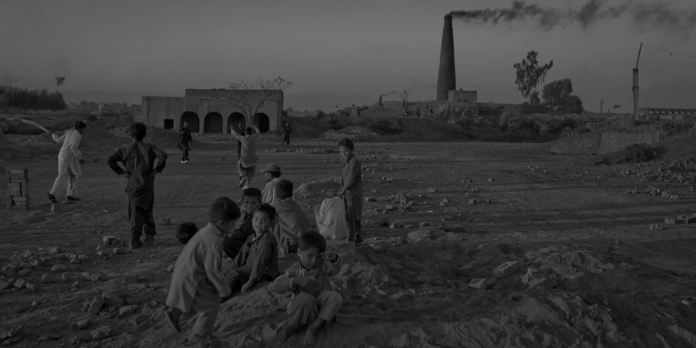 Pakistani children watch a cricket game at a brick factory on the outskirts on Rawalpindi on November 12, 2011.