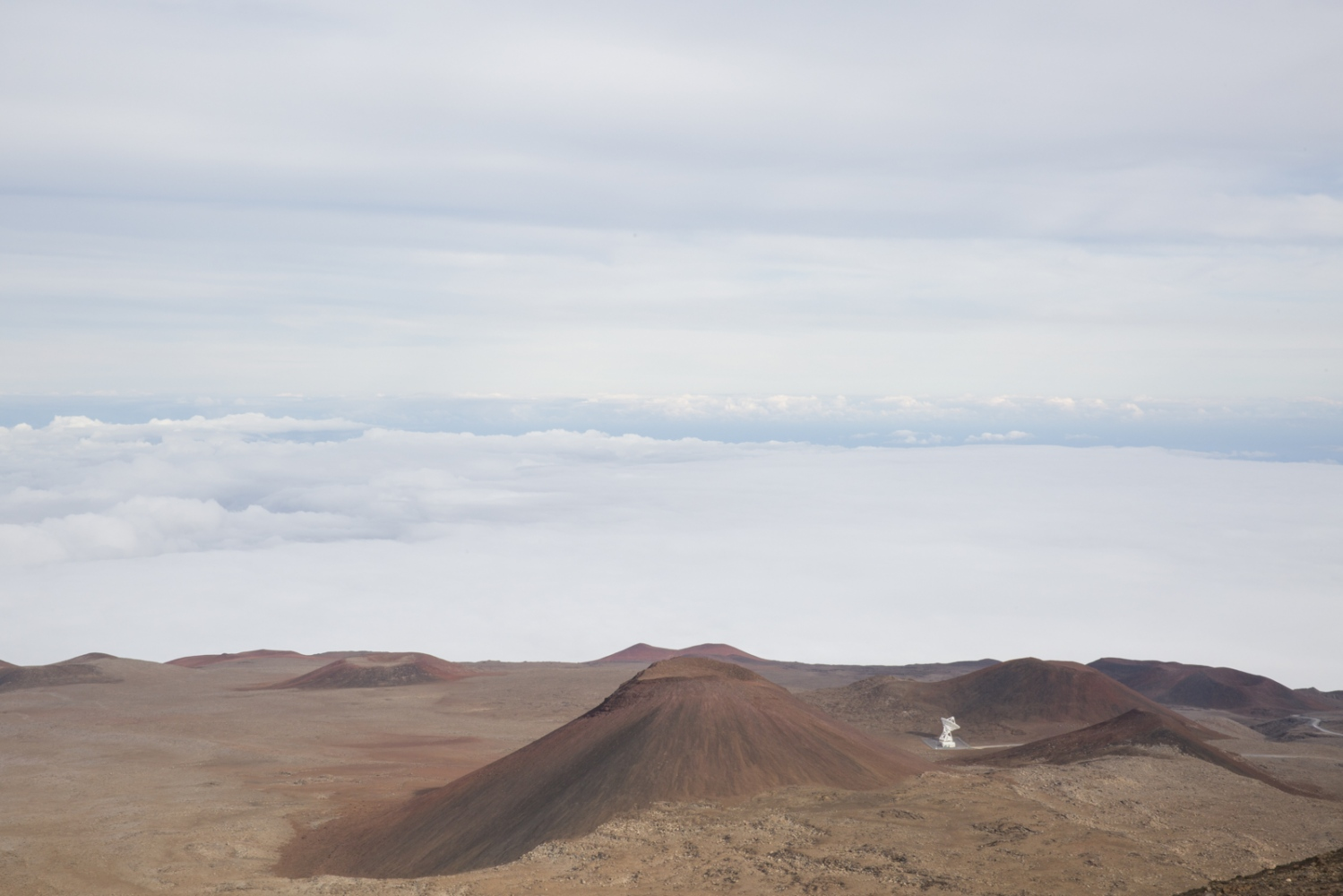 A landscape with a dormant crater and a satellite is photographed from the top of volcano Mauna Kea, about a million years old, which raises 13,796 ft above sea level. Hawaii, Big Island.