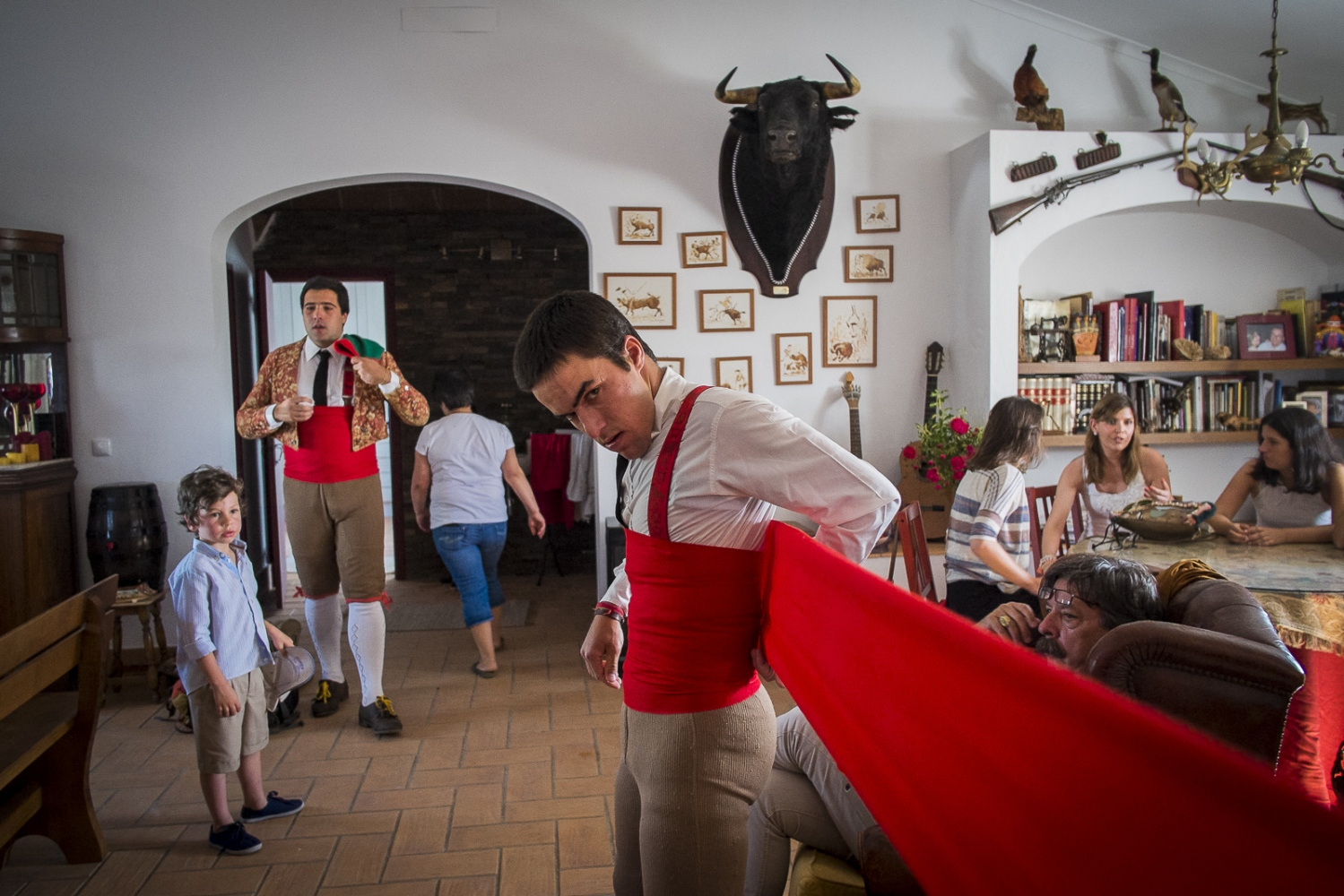 João Madeira, member of the Grupo Forcados Amadores de Évora (GFAE) puts a 5 meters red waistband protection in the house of an old member of the group before the bullfight. The waistband helps to protect their internal organs from the attack of the bull.