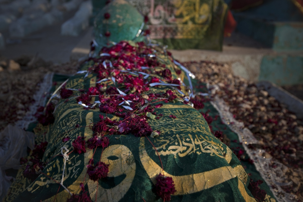 Flowers and a shroud cover a grave at the shrine of spiritual leader Hazrat Abdullah Shah Ashabi in Makli in the district of Thatta in Pakistan's Sindh province on November 25, 2011.