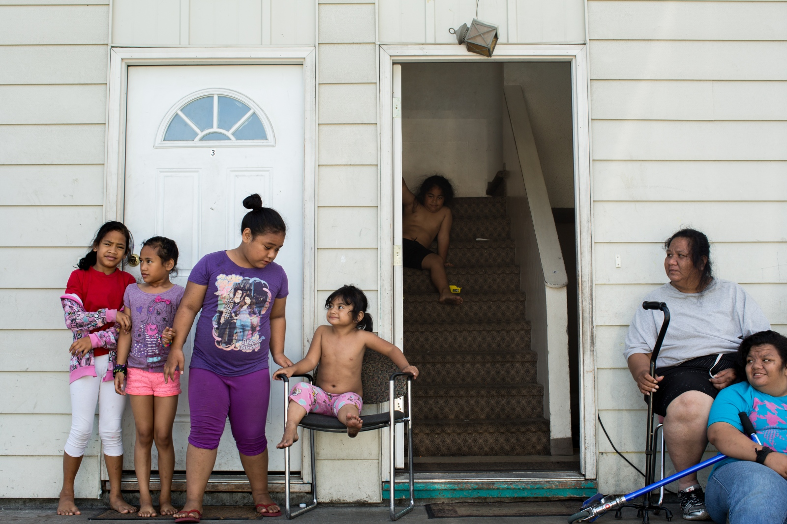"Alofa Lolo (second to right) sits outside with her children, nieces, and nephews in Mountain View. Lolo came to Alaska from Samoa, and has eight children who have all been born in the U.S.. Her oldest, Nicole Lolo (right), 18, is disabled, and her youngest will be 3 this month. ""I sit outside with the children because of the cars,"" she says. ""They drive by so fast and do not see the children."""