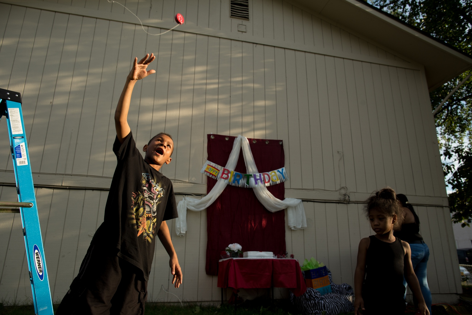 Wayne Rodriguez, 10, tosses a yo-yo into the air while family and friends prepare for his uncle's birthday party in Mountain View.