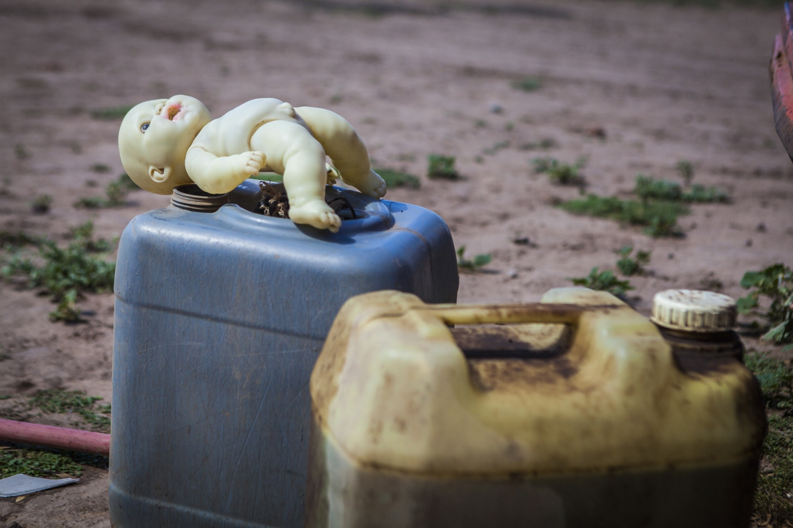 A doll sits on top of containers with gasoline. Children play freely in the Guaycurú Indigenous Community, but sometimes dangerous are closer than you will imagine.