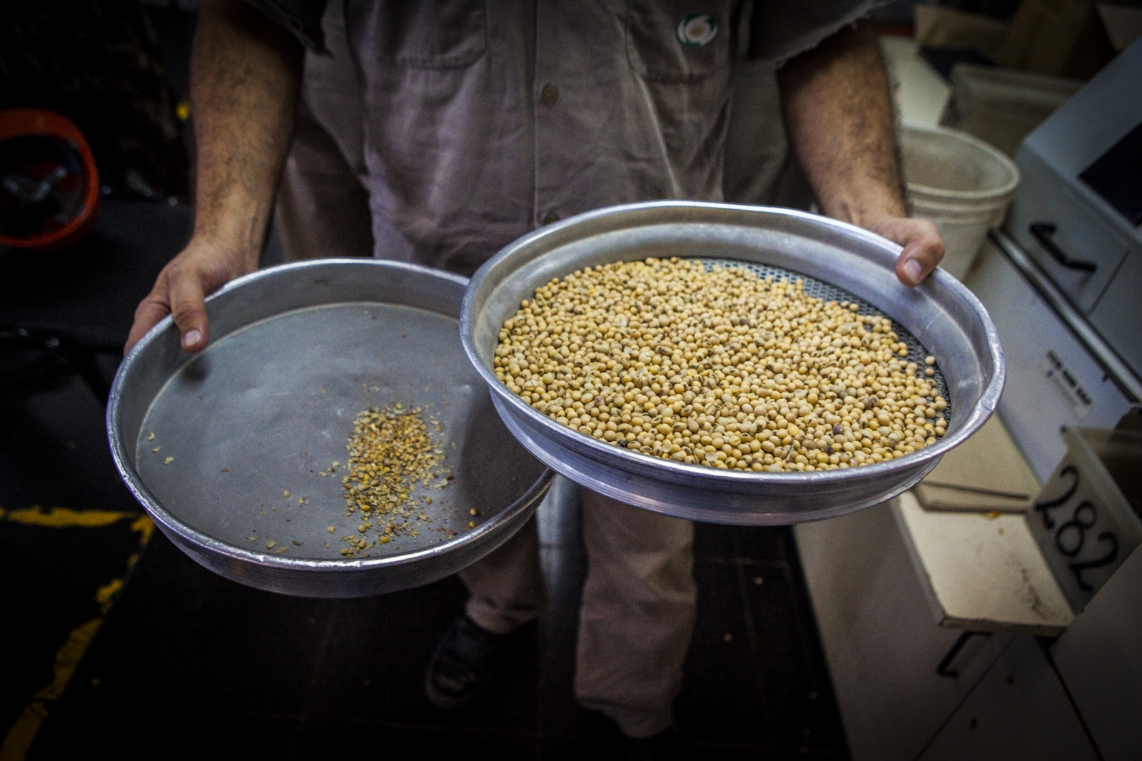 A worker strains a sample of soybeans to get rid off impurities, inside the testing office at Terminal 6 of the General San Martín Port, San Lorenzo. These is done to understand the quality of the grains delivered and the value of the cargo, previously hoovered from a truck. Around 1,300 trucks deliver grains at Terminal 6, representing 40,000 tons a day, which is half of the capacity that the port can recive in one single day. Terminal 6 is the largest of its kind in South America where 80,000 tons per day are received by trucks, trains and boats. The grains are then process at the plant located at the port and then shipped worldwide.